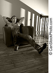 Young man relaxing on a chair - Young man lazing around in...