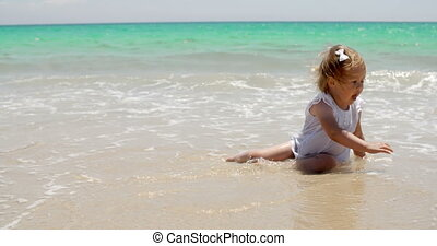 Little girl sitting on a beach close to the water - Little...