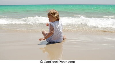 Little girl romping at the edge of the surf on a sunny...