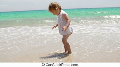 Adorable little girl playing in the surf