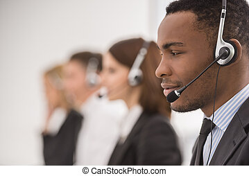 Call center - Line of phone operators with headsets work at...