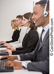 Call center - Attractive positive young colleagues working...