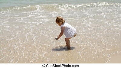 Little girl playing in the sea bending over at the edge of...