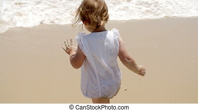 Little girl paddling in shallow surf - View from behind of a...