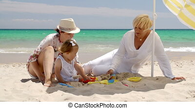 Small Family Having Fun at the Beach Sand - Little Girl...