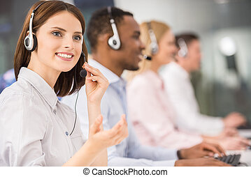 Call center - Beautiful young lady talking on headset at...