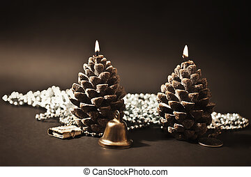Two candles as a candle with christmas-tree decorations on...