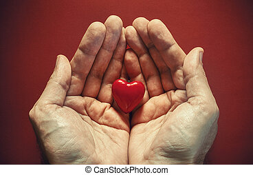In the Name of Love - Two male hands holding red wooden...