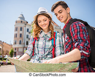 Travel - Happy young travelers sightseeing city with map....