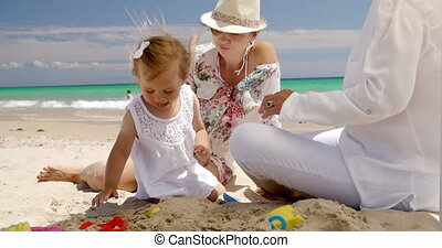 Girl Resting at the Beach with Mom and Grandma - Cute Little...
