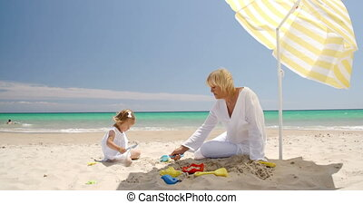 Little girl playing with her granny on the beach - Cute...