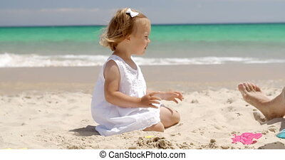 Little girl playing on a tropical beach - Little blond girl...
