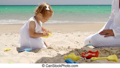 Pretty little girl paying in the beach sand in a fresh white...