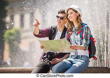 Travel - Young tourist couple use their map to determine...