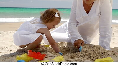 Little girl digging in golden beach sand - Little girl...