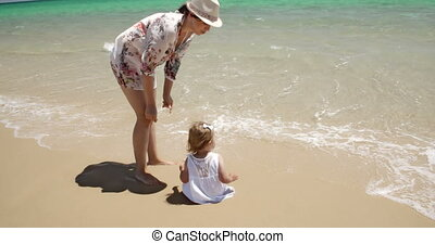 Mom Watching Over her Girl Enjoying at the Beach - Caring...