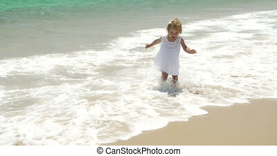 Little girl running along a beach with her mother