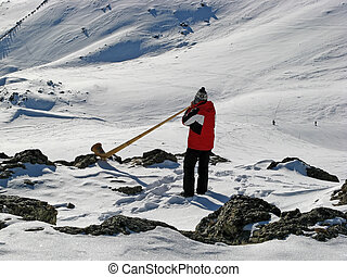 Man playing alp horn in the snowy mountains