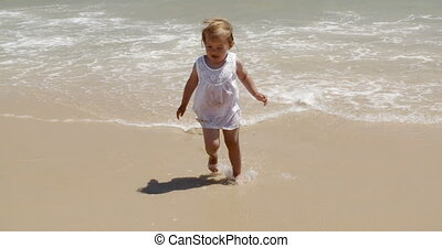 Cute little girl pointing out to sea as she stands barefoot...