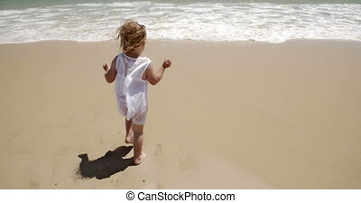 Small girl enjoying herself at the seaside walking across...