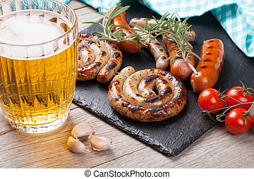 Beer mug and grilled sausages on wooden table