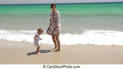 Young mother with her daughter at the sea