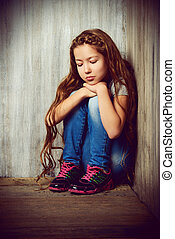 awkward age - Portrait of a sad girl child sitting in the...