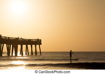 Paddle Boarding - Silhouette of a man paddle boarding in the...