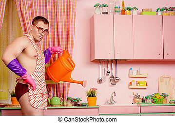 watering the flowers - Muscular man in an apron watering the...