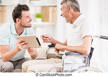 Old man at hospital - Smiling handsome man showing digital...