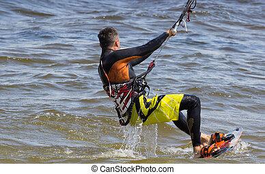 Kitesurfing - kitesurfer glides view from the back. Ukraine