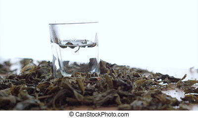 Tea leaf dissolving in hot water on white background