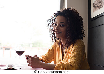 woman with smartphone in restaurant - Afro woman typing on...