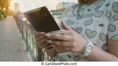 Women using tablet PC backlit by sun - Women using tablet PC...