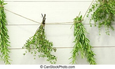 Single twigs of Thyme and Rosemary on Wooden Board.