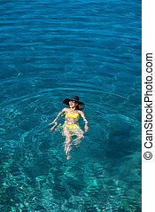 Woman swimming in the sea - Young woman in yellow swimsuit...