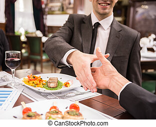Business lunch - Two elegant business partners shaking hands...