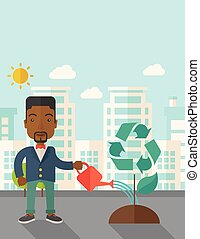 Man watering a recycling tree - A black man watering the...