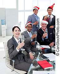 Manager and his team with novelty Christmas hat toasting at a party in the office