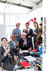 Business people with novelty Christmas hat toasting at a...