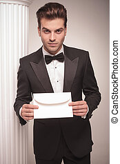 Handsome young business man giving you a white envelope. -...