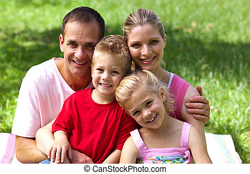 Close-up of a happy family smiling at the camera in a park