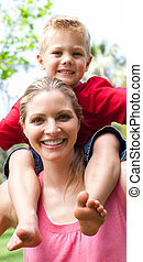 Close-up of a mother giving her son a piggyback ride in a park