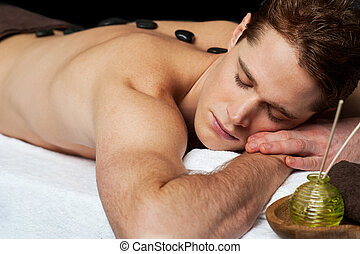 Man relaxing at spa. - Young man getting a stone massage at...