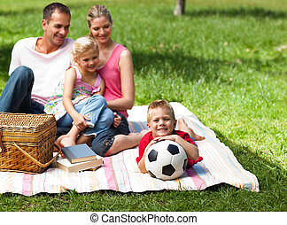Happy parents and children picnicing in the park and smiling...