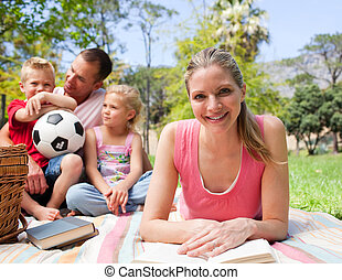 Smiling woman reading at a picnic with her family in the...