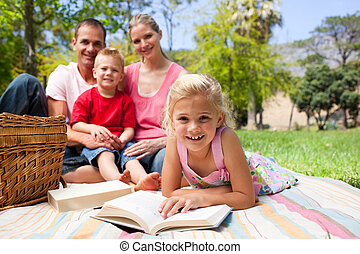 Cute little girl reading lying on the grass while having a picnic with her family in a park