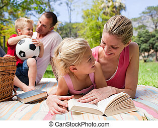 Mother and her daughter reading at a picnic with their...