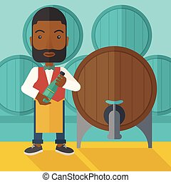 African Wine maker inspecting wine from barrel - An african...