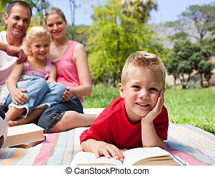 Smiling little boy reading lying on the grass while having a picnic with his family in a park